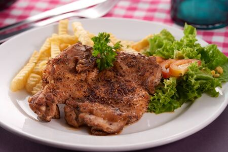 Photo for grilled chicken chop served with potato fries and salad. - Royalty Free Image