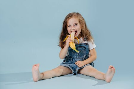 Photo pour Adorable happy barefoot little preschooler girl with brown wavy hair is eating banana, sitting on the floor with legs spread. She wears jeans overalls and white shirt. over blue background - image libre de droit